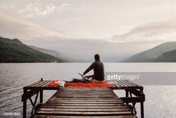 man sitting on a masai blanket on a wooden jetty at a scottish highlands loch - back stock pictures, royalty-free photos & images