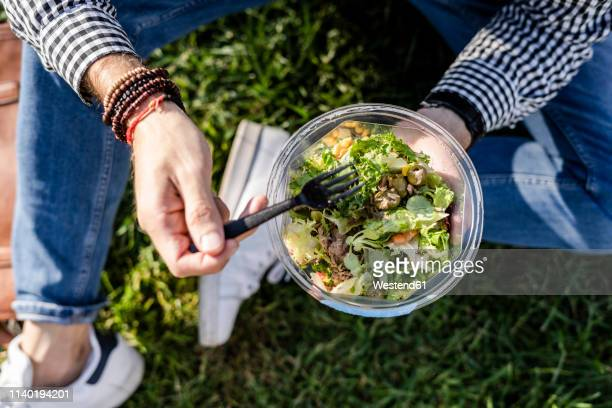man sitting on a meadow eating mixed salad, partial view - salad stock pictures, royalty-free photos & images
