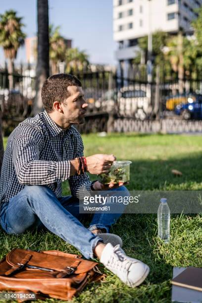 man sitting on a meadow in city park eating mixed salad - lunch stock-fotos und bilder