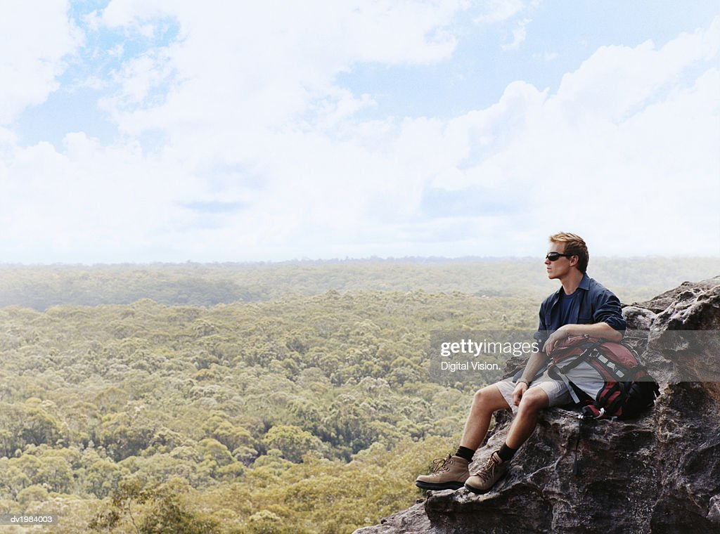 Man Sitting on a Mountain Summit Looking at View : Stock Photo