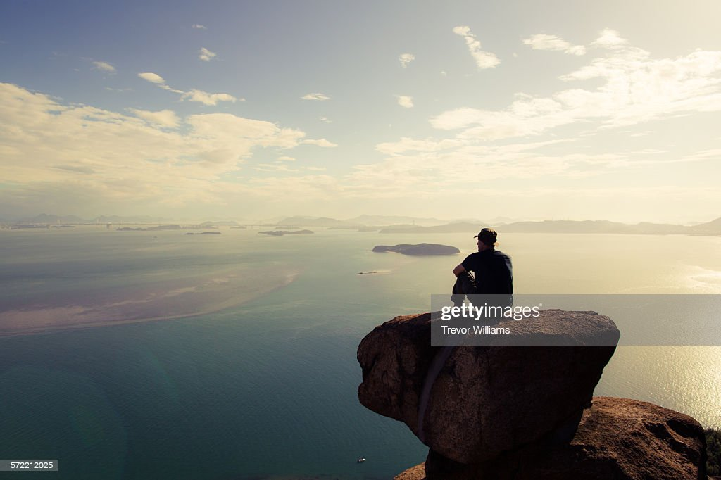 A man sitting on a mountain wtching the sun set : Stock Photo