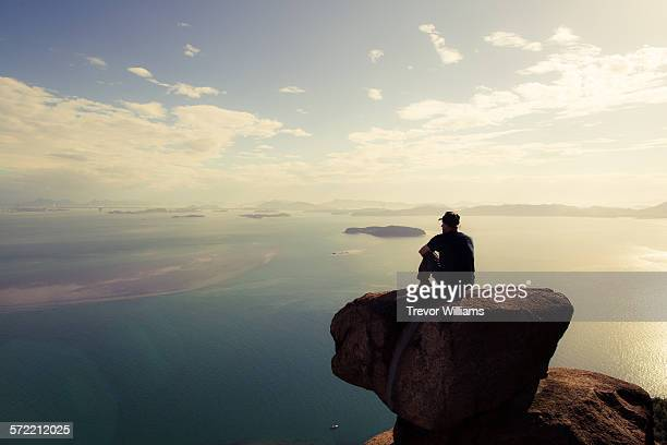 a man sitting on a mountain wtching the sun set - on top of stock pictures, royalty-free photos & images