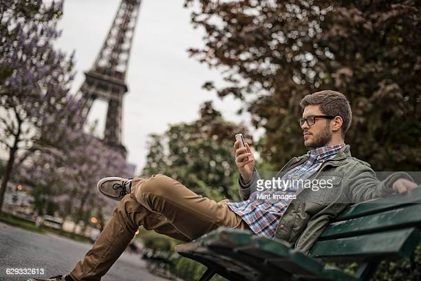 A man sitting on a park bench in the Champs de Mars under the Eiffel Tower.