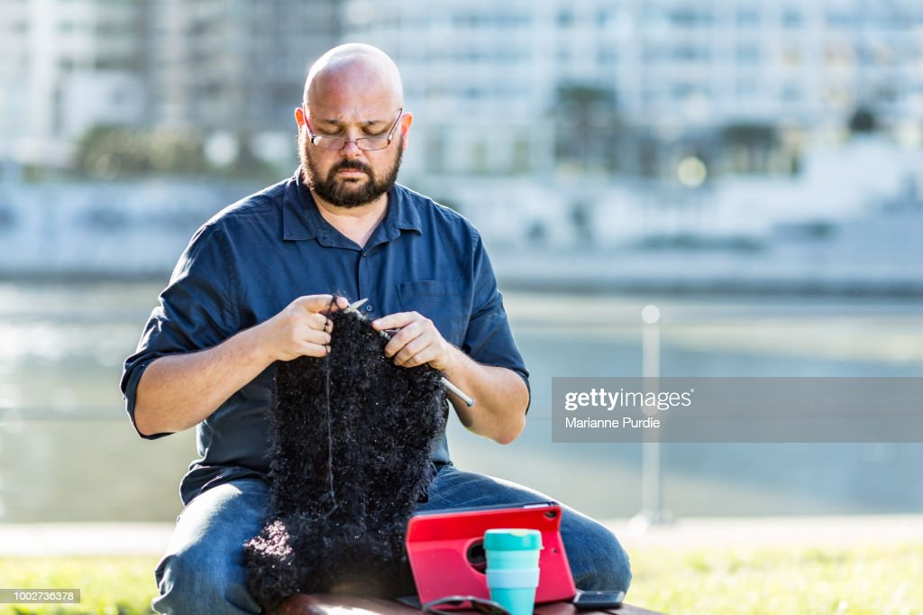A man sitting on a park bench knitting : Stock-Foto