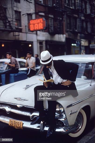 A man sitting on a Plymouth car and reading a book in New York City