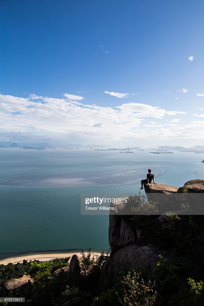 A man sitting on a rock at the edge of a cliff : Stock Photo