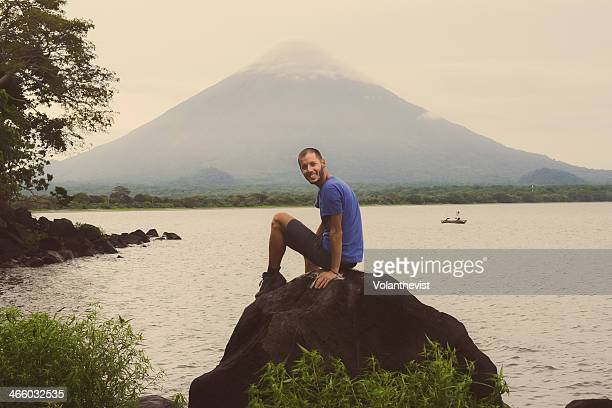 Man sitting on a rock, Concepcion volcano behind