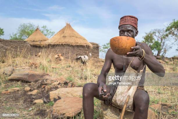 Man sitting on a rock drinking local beer in a calabash during the circumcision ceremony a rite of passage from boys to men practised in many African...
