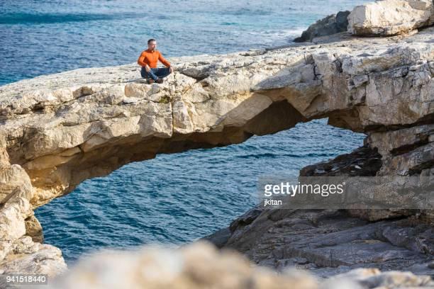 mann sitzt auf einer felsformation unter dem meer - insel gozo malta stock-fotos und bilder