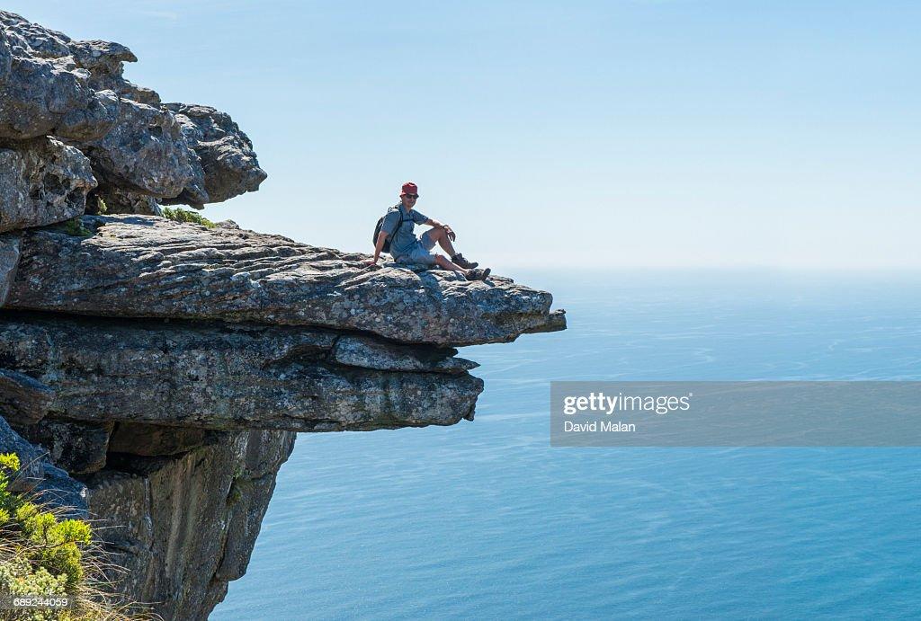 Man sitting on a rock ledge. : Stock Photo
