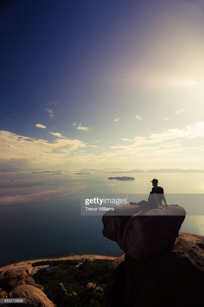 A man sitting on a rock on a mountain top : Stock-Foto