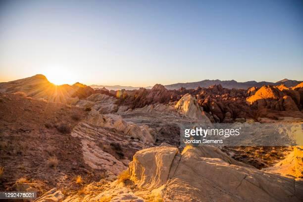 a man sitting on a rock watching the sunrise in the desert. - nevada stock-fotos und bilder