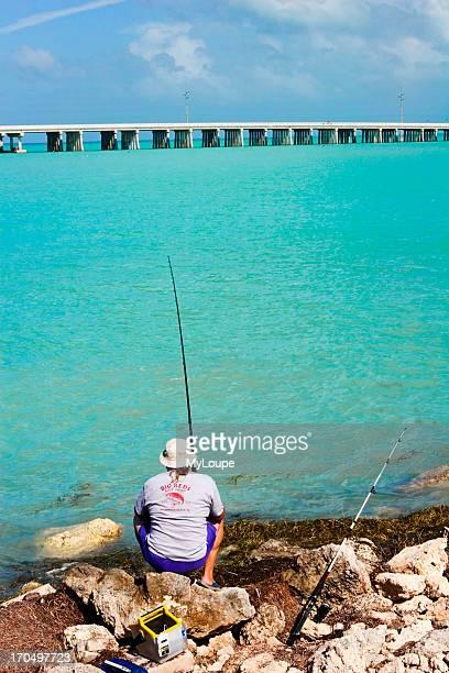 Man Sitting On A Rocky Beach In Bahia Honda State Park In The Florida Keys Looking At The Seven Mile Bridge Near Marathon Fl