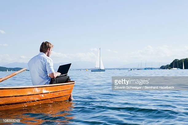 man sitting on a rowboat using laptob - starnberg photos et images de collection
