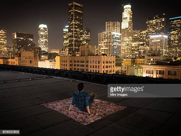 A man sitting on a rug on a rooftop overlooking a city lit up at night.