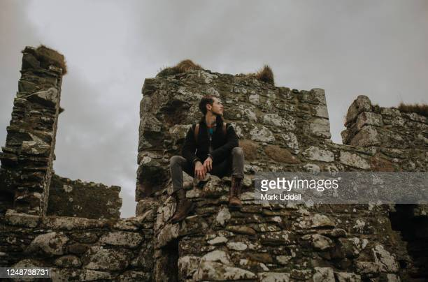 man sitting on a ruined wall at dunnottar castle, scotland - dunnottar castle stock pictures, royalty-free photos & images
