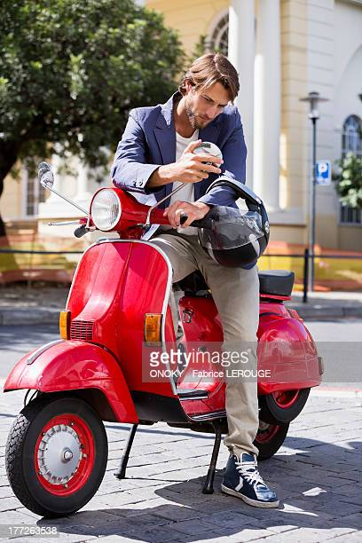Man sitting on a scooter looking at a mirror