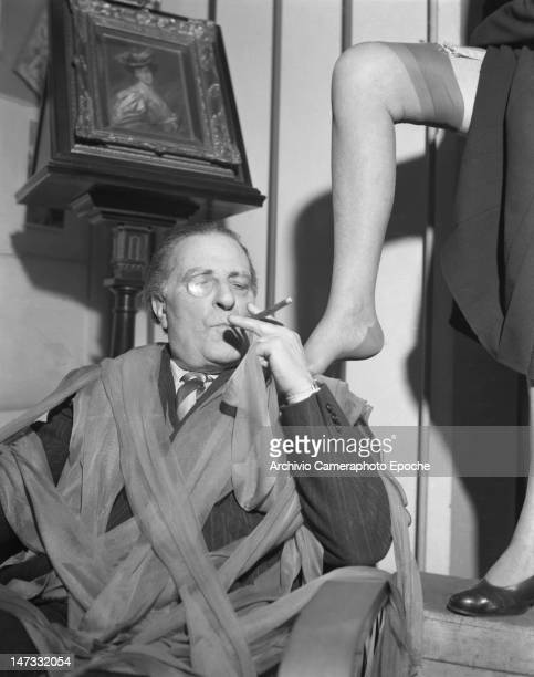 A man sitting on a sofa and smoking a cigar wrapped in tights a model leg leaning on his shoulder Museum of Famous Tights Milan 1950