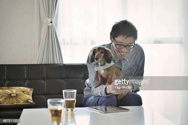 man sitting on a sofa and using the smartphone - alleen één mid volwassen man stockfoto's en -beelden