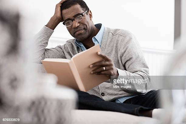 A man sitting on a sofa at home, reading a book.