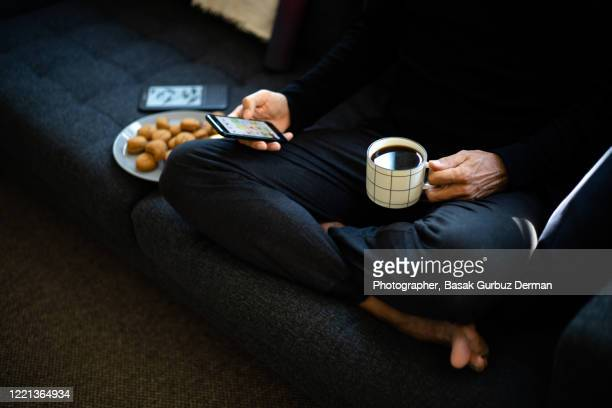 a man sitting on a sofa, drinking coffee, eating cookies, using mobile phone - tranquil scene stock pictures, royalty-free photos & images