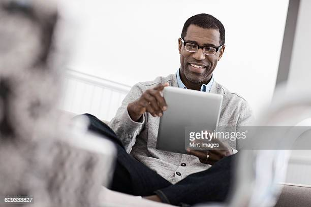A man sitting on a sofa, using a digital tablet.