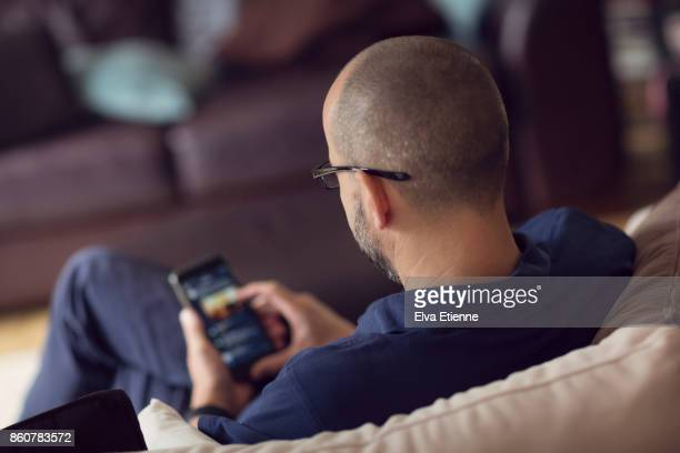Man sitting on a sofa whilst browsing on a smartphone