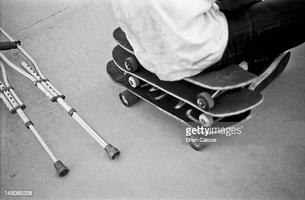 A man sitting on a stack of skateboards next to crutches