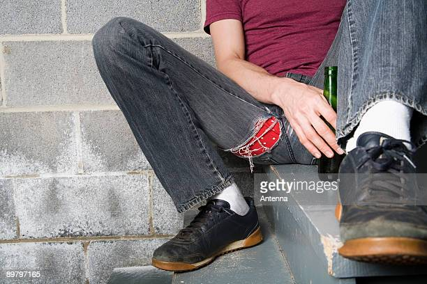 A man sitting on a step and holding a bottle of beer
