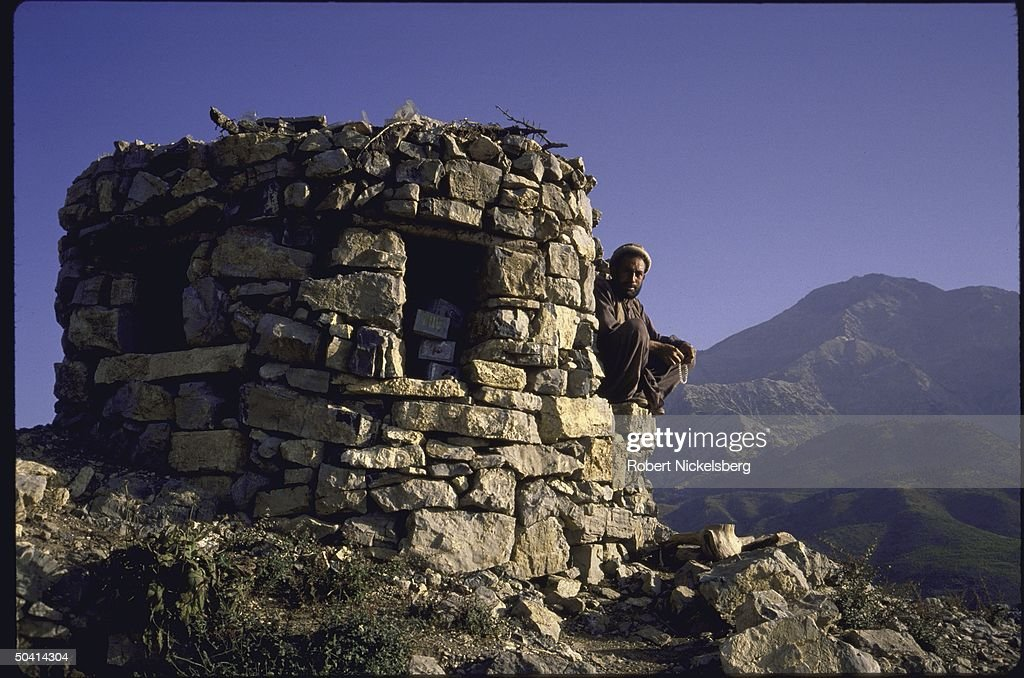 A man sitting on a stone structure in an : News Photo