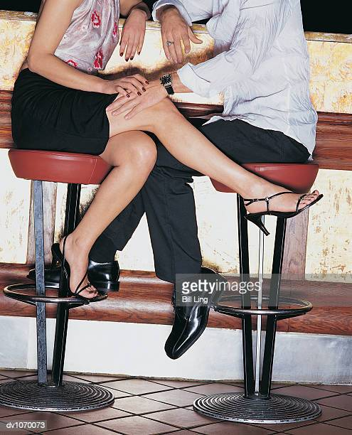 man sitting on a stool at the bar counter touching a woman's leg - man touching womans leg stock photos and pictures