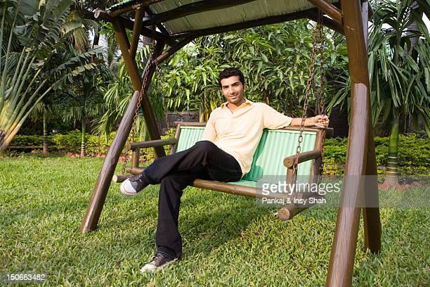 Man sitting on a swing in the garden