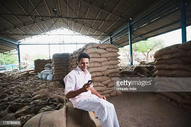 Man sitting on a wheat sack and reading a SMS in a warehouse, Anaj Mandi, Sohna, Gurgaon, Haryana, India