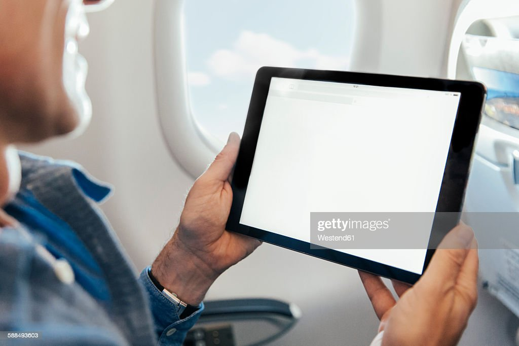 Man sitting on an airplane holding digital tablet : Stock Photo