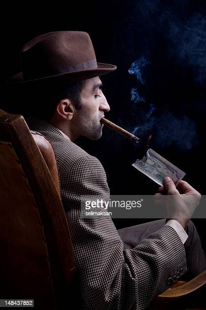 Man sitting on armchair smoking cigar with burning dollar bill