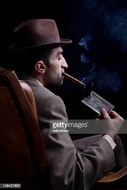 Mann sitzt auf Sessel Rauchen Zigarre mit brennenden dollar-Schein