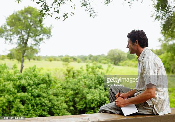 Man sitting on balcony holding notebook, smiling