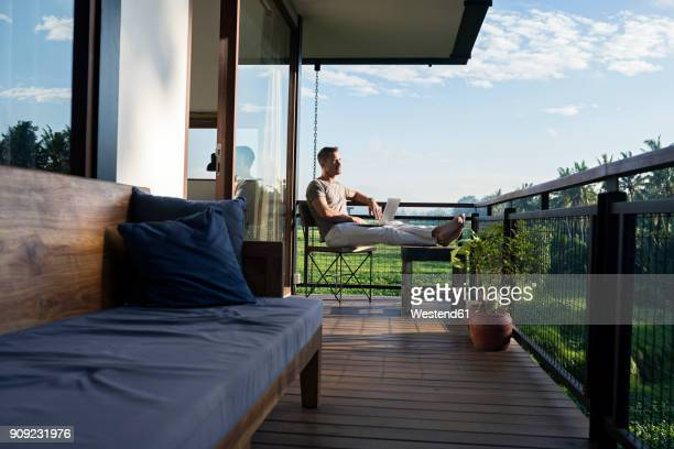 man sitting on balcony of modern house looking landscape, holding laptop - holiday villa stock pictures, royalty-free photos & images