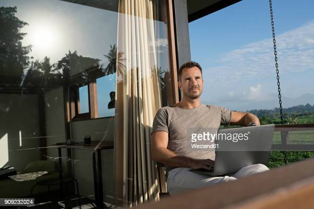 Man sitting on balcony of modern house looking landscape, holding laptop