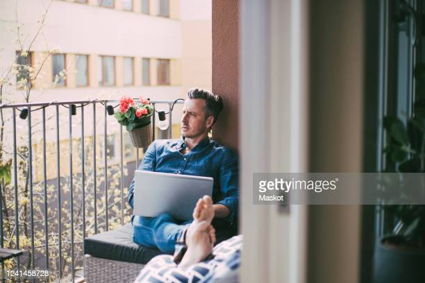man sitting on balcony with laptop looking out - hommes d'âge moyen photos et images de collection