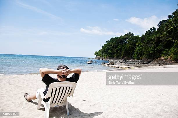 Man Sitting On Beach And Looking At Sea