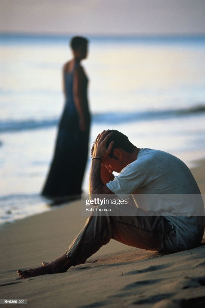 man walking away from a woman man sitting on beach holding his head woman walking away 3454