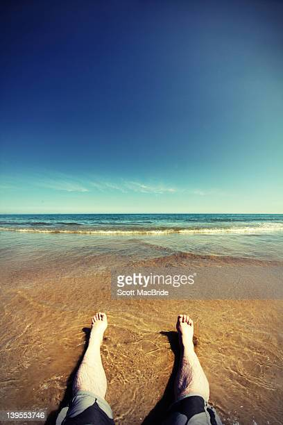 man sitting on beach waiting for wave to come - scott macbride stock pictures, royalty-free photos & images