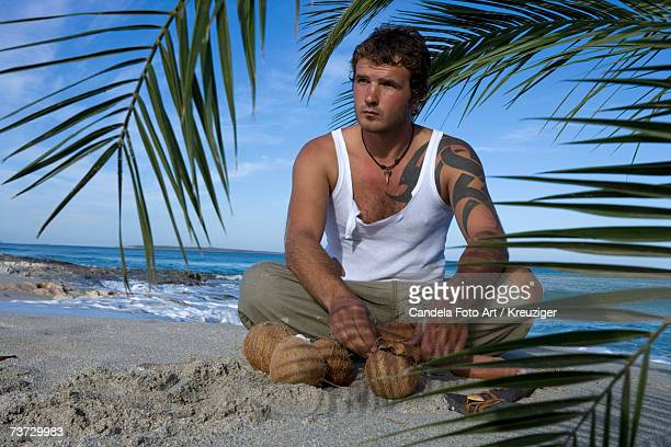 Man sitting on beach with coconuts