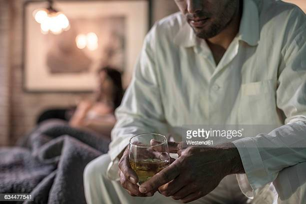 man sitting on bed having a drink - alcoolismo - fotografias e filmes do acervo