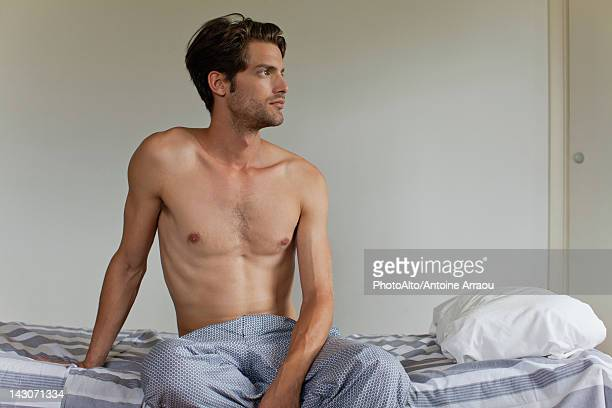 Man sitting on bed, looking away in thought