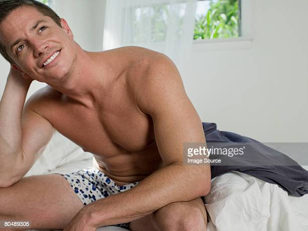 man sitting on bed - boxershort stock pictures, royalty-free photos & images