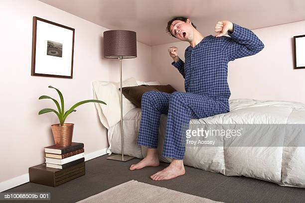Man sitting on bed stretching in miniature bedroom