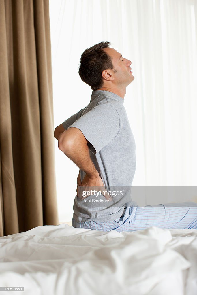 Man sitting on bed with backache  : Stock Photo