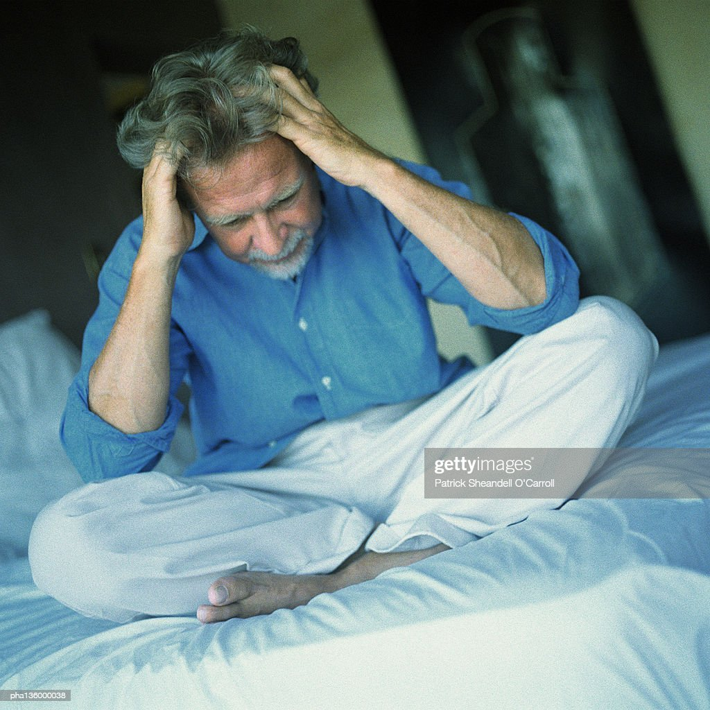 Man sitting on bed with legs crossed, both hands pulling at hair : Stockfoto